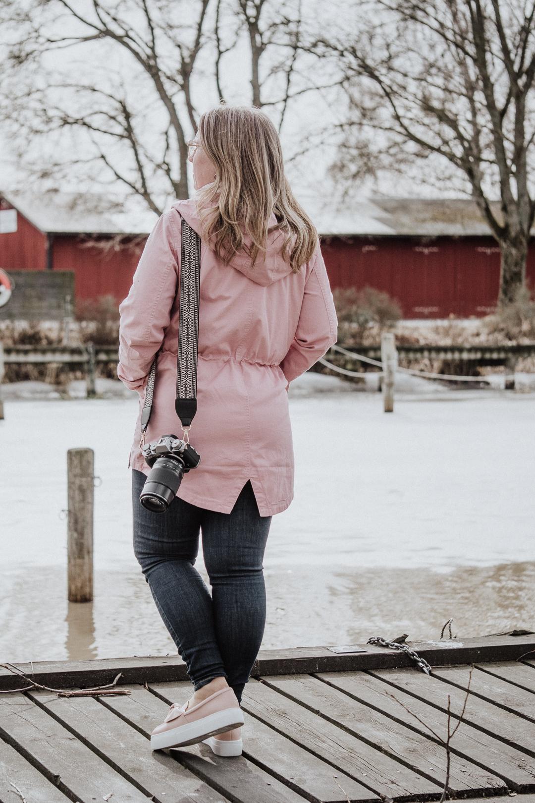 Ta på en rosa parkas, rosa sneakers och använd en väskrem från Glitter som kamerarem i vårsolen